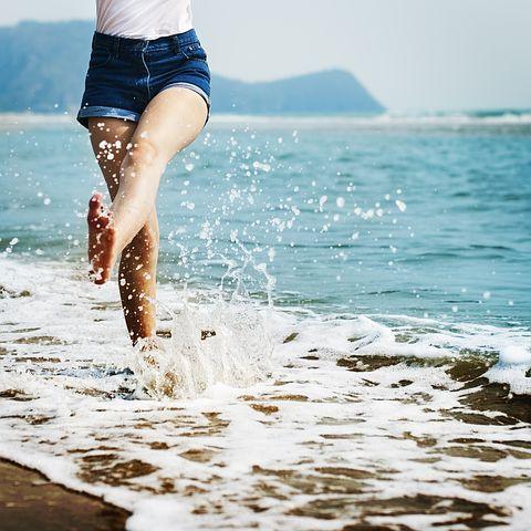 Chica andando en la arena de la playa para cuidar pies