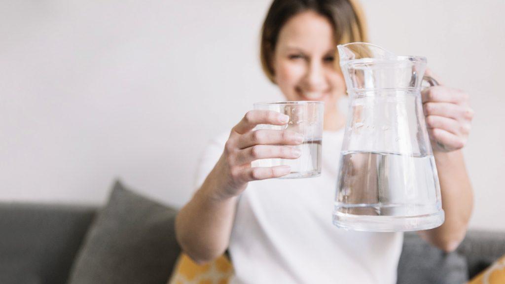 Mujer sirviendo vaso de agua