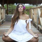 Mujer realizando meditación logrando una vida balanceada