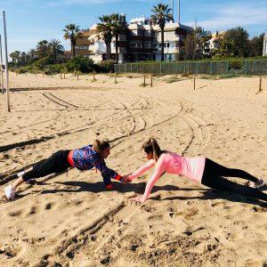 Elo Soares, influencer y entrenadora personal, aparece realizando ejercicio físico y trabajo de entrenamiento personal con otra clienta en la arena de una playa.