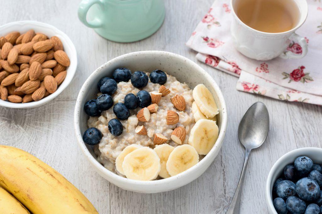 Bowl con arándanos, bananas, avena, frutos secos