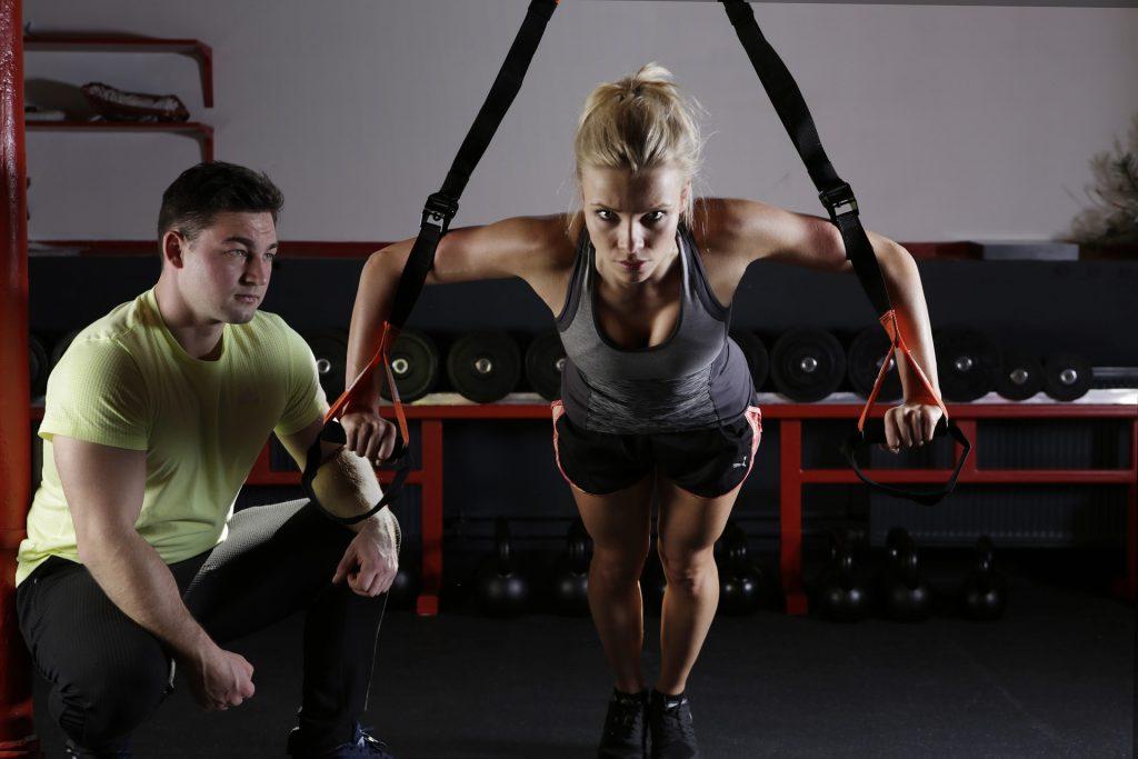 Mujer realizando ejercicio físico en un gimnasio motivada por su entrenador