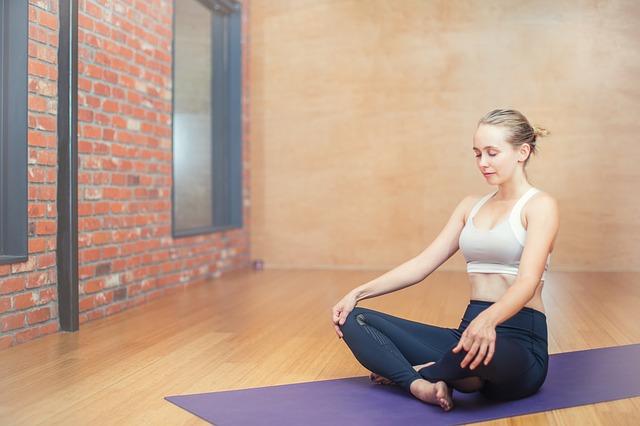 Mujer realizando la meditación sobre esterilla de yoga