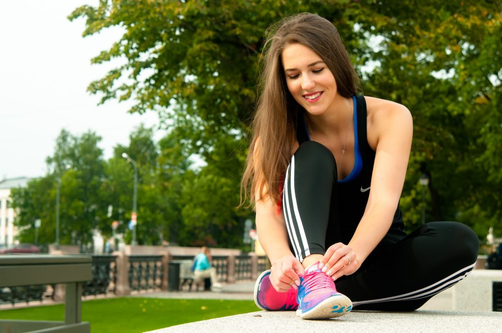 Mujer adulta en ropa deportiva se ata las zapatillas deportivas para hacer ejercicio