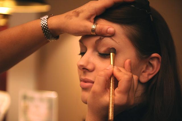 Mujer siendo maquillada por un profesional