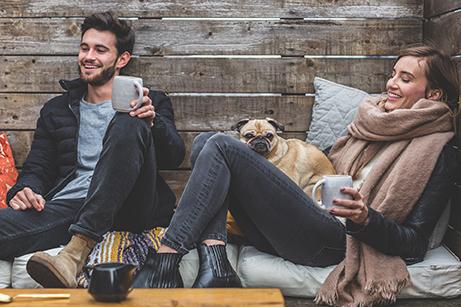 Pareja tomando un café con ropa de invierno y con su mascota. ¿Aceptamos el amor que creemos que merecemos?