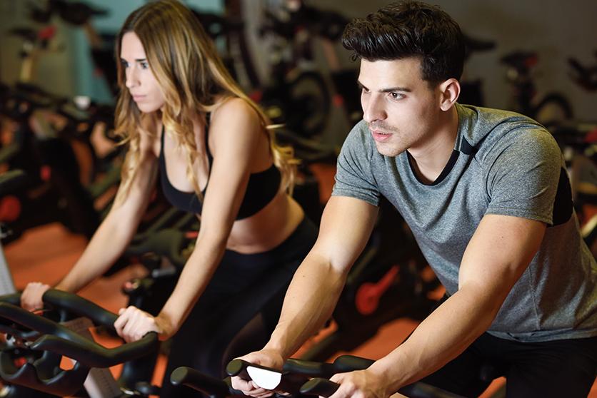 Hombre y mujer jóvenes realizando ejercicios físico en la bici estática del gimnasio