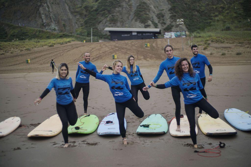 Quique Guijarro con el grupo de la escuela de surf La Salbaje Surf Eskol. Todos preparados en la arena con las tablas de surf para hacer bodysurf.