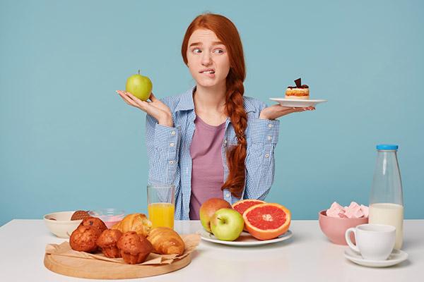 joven dudando de comer saludable o pastelitos