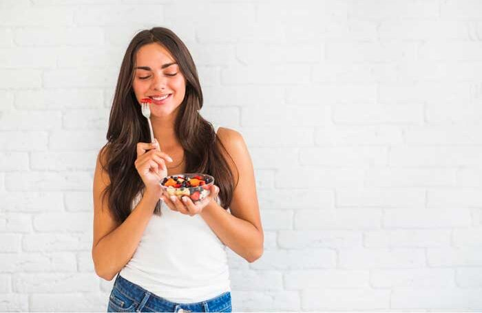 Una chica comiendo comida sana para un estilo de vida saludable