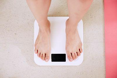 Persona pesandose por culpa de exceso de azucares en los alimentos