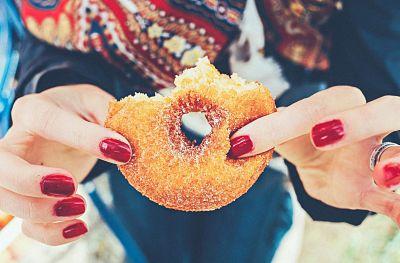 azucares en alimentos, mujer sosteniendo una dona