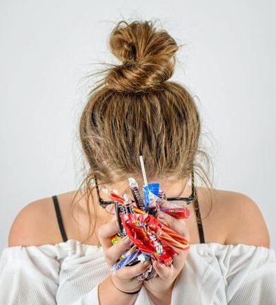 mujer con dulces con adicción al azúcar